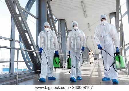 Covid-19, Pandemic, Workers In Hazmat Suits Carrying Barrels And Disinfecting All Surfaces In The Ci