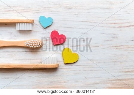 Bamboo Toothbrushes Family Set With Colorful Wood Hearts On Vintage Wood Background. Natural Product