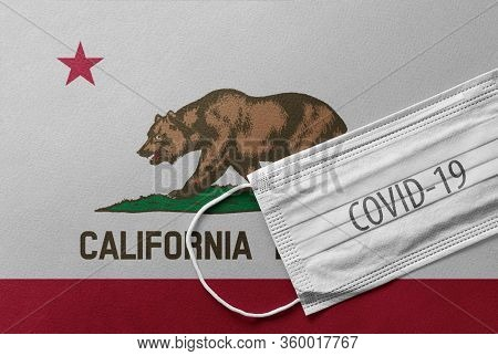 Face Medical Surgical White Mask With Covid-19 Inscription Lying On California State Flag. Coronavir
