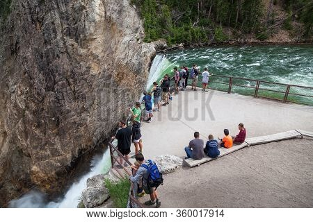 Yellowstone National Park, Usa - July 12 2014:  Tourists Stand And Sit On An Overlook At The Top Of