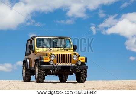Shoshone National Forest, Wyoming, Usa - July 13, 2014:  A Gold Jeep Rubicon In A Dirt Parking Area