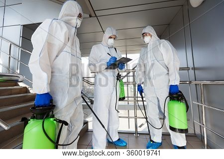 Outdoor Disinfection By Cleaning Workers In Hazmat Suits, Surface Treatment From Coronavirus, Steam