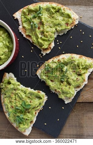 Fresh Guacamole Sauce With Peas Microgreen And Sesame Seeds On Three Toasted Tortillas On A Black Sl