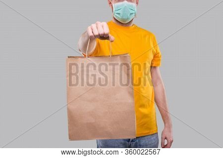 Delivery Man Wearing Medical Mask. Yellow Tshirt Delivery Boy. Food Delivery. Home Delivery. Paper B