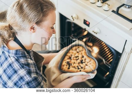 Young Blonde Woman Taking Heart Shaped Berry Pie Out Of The Oven. Cooking At Home And Smiling.