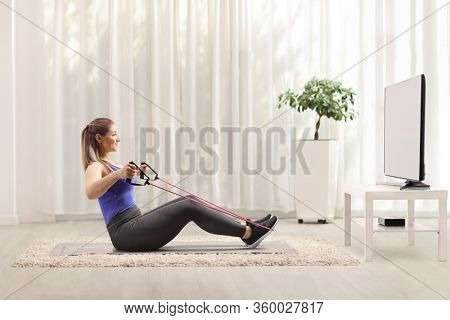 Woman sitting on the floor and exercising with a resistance band in front of a tv at home