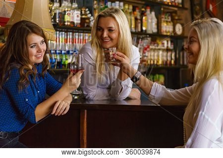 Happy Girls Best Friends Drinking Alcohol In Night Club, Gossiping And Talking At Counter With Bar E