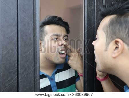 A Man Looking At His Reflection In Mirror Nose Picking And Checking His Nasal Cavity For Nose Infect