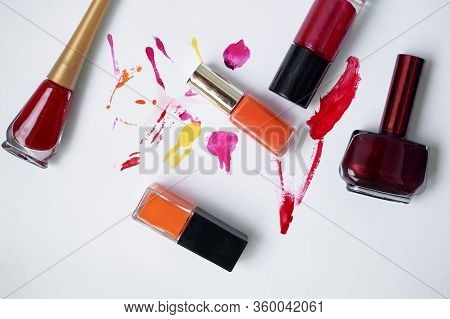 Lucky On A White Background, With Smears Of Varnish. Orange, Burgundy, Red. Choosing Varnishes For M