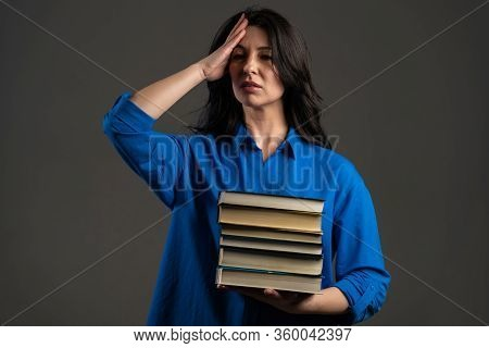 European Bored Mature Woman As Student On Grey Background Is Dissatisfied With Amount Of Homework An
