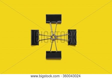 Four Black Paper Clips For Office Stationery Lying Isolated On Yellow Background. Free Copyspace. Co