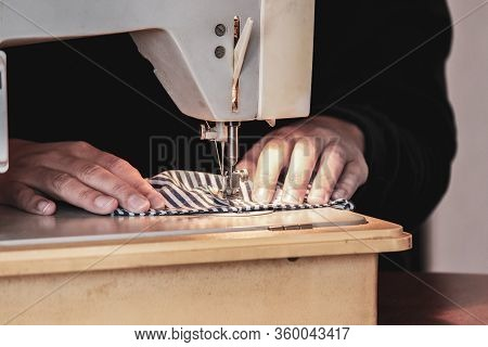 Woman Hands Using The Sewing Machine To Sew The Face Medical Mask During The Coronavirus Pandemic. H