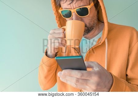 Man Drinking Coffee And Using Mobile Phone In Morning, Adult Male With Yellow Zip Hoodie Holding Cof