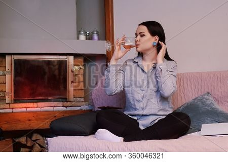 A Girl Sits On A Sofa At Home And Drinks Rose Wine Against The Background Of The Fireplace. Stay At