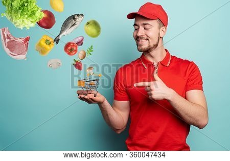 Deliveryman Holds A Small Cart That Is Filled With Food. Cyan Background