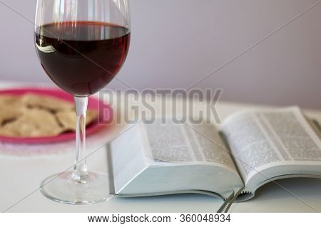 A Glass Of Dry Red Wine And Broken Unleavened Bread Lie On A Plate. To Celebrate The Lord's Supper.