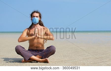 COVID-19 epidemic, a man in a surgical mask meditates, keep calm and hygiene.