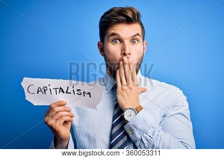 Young blond businessman with beard and blue eyes holding paper with capitalism message cover mouth with hand shocked with shame for mistake, expression of fear, scared in silence, secret concept