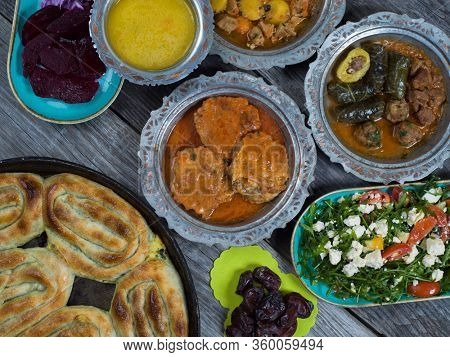 Eid Mubarak Traditional Ramadan Iftar dinner. Assorted tasty food in authentic rustic dishes on wooden table background.  Turkish Bosnian food meat kebab, pita, Sarma, klepe, sogan dolma.
