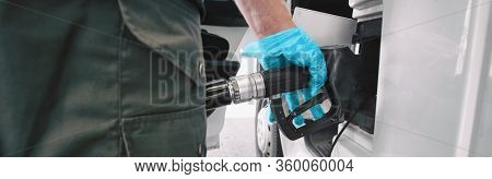 Gas pump Coronavirus outbreak protection gloves for touching handle while pumping gasoline at gas station banner panoramic. Low prices of crude oil plunging during COVID-19 pandemic.