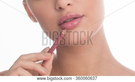 Beauty Concept. Unrecognizable Woman Putting On Makeup, Using Nude Lip Liner Pensil, Isolated Over W