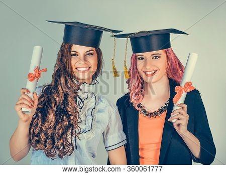 Portrait Closeup Beautiful Happy  Graduates, Two Graduated Student Girls, Young Women In Cap Gown Tu