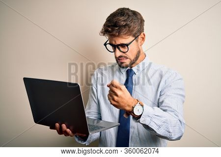 Young businessman wearing glasses working using laptop standing over white background annoyed and frustrated shouting with anger, crazy and yelling with raised hand, anger concept
