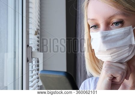 Woman In Surgical Medical Face Mask Staying At Home Near The Window And Using Smartphone, Reading Ne