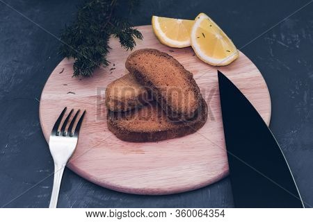 Dry Toasted Bread With Sauce, Seasonings And Lemon Against A Dark Gray Stone Background, With A Knif