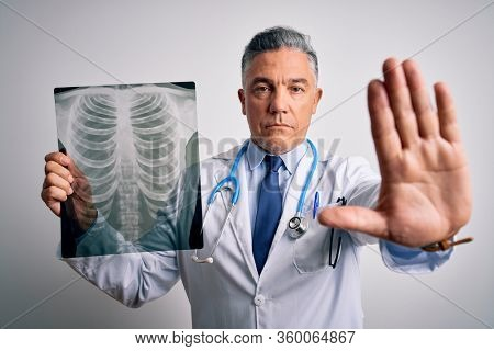Middle age handsome grey-haired doctor man holding chest xray over white background with open hand doing stop sign with serious and confident expression, defense gesture