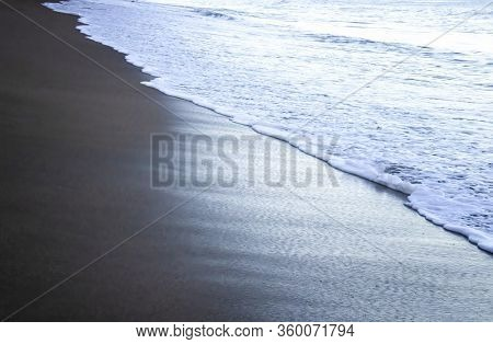 Close Up Of White Foamy Edge Of Surf On Wet Sand At Daybreak In Hawaii.