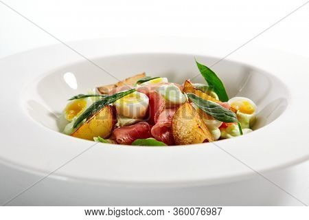 Tuna salad, baked potatoes and boiled quail eggs. Plate with tasty fish and spinach. Delicious seafood served with sauce and greenery. Traditional mediterranean cuisine dish on table