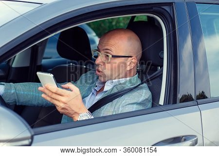 Scared Funny Looking Young Man Driver In The Car About To Make An Accident Talking Texting On Phone.