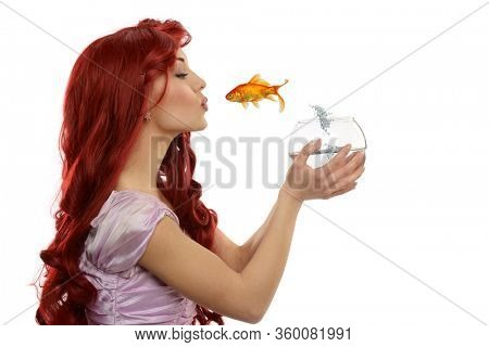Young redhead princess kissing a jumping fish isolated on a white background