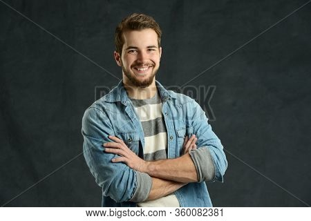 Young man cassually dressed smilingwith arms crossed agains a gray background