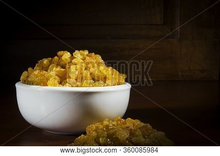 Light Raisins In A White Ceramic Bowl On A Wooden Background