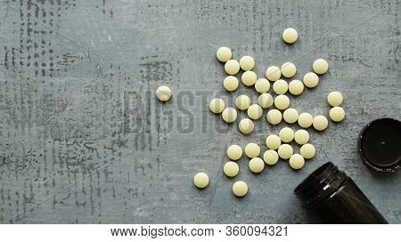 Yellow Round Tablets Or Pills Vitamins Flat Lay On Blue Stone Concrete Table With Black Plastic Bott