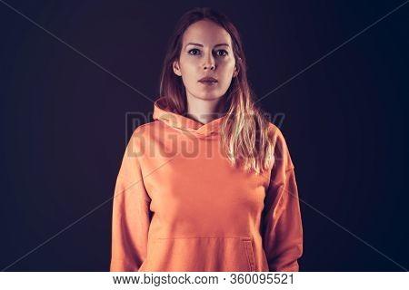 Closed Portrait Of Yong Adult Woman On Dark Background Wearing Orange Hoodie