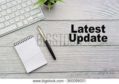 Latest Update Text With Notepad, Keyboard, Decorative Vase And Fountain Pen On Wooden Background. Bu