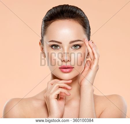 Portrait of beautiful  girl which touching her fresh face. Beautiful face of caucasian woman with healthy skin. Closeup face of young woman with clean skin. Skin care.