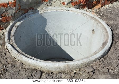 Installation Of A Water Main Sewer And Drain. A Close-up On A Concrete Sewer Well, Ring In The Groun