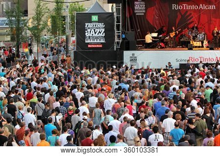 MONTREAL, CANADA - JUNE 29: People look at a show during the open-air concert at the 33th International Jazz Festival of Montreal on June 29, 2012 in Montreal, Canada