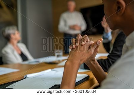 Shallow Depth Image Of African Businessman Holding Hands Together In Boardroom Meeting While Listeni