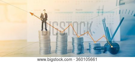 Double Exposure Of Miniature Business Man On Stack Of Coins And Analog Clock For Business And Financ
