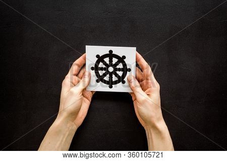 Wheel Of Dharma - Buddhist Religion Symbol - In Hands On Black Table Top View