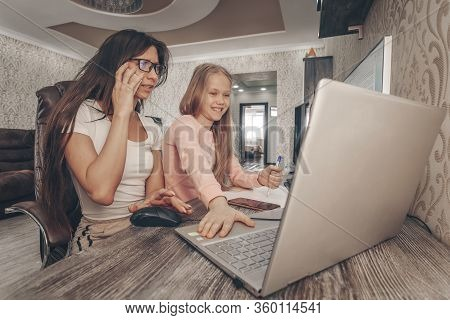 Stay At Home Mom Working Remotely On Laptop While Taking Care Of Her Baby. Young Mother On Maternity
