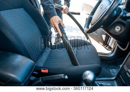 Man Vacuuming, Hoovering A Car Interior By Vacuum Cleaner, Cleaning Concept
