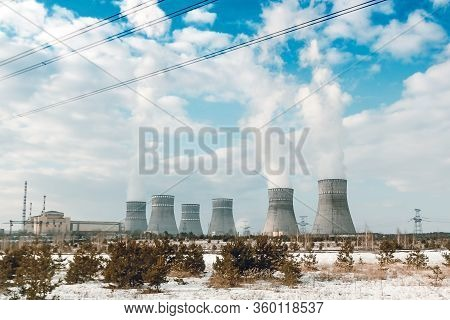 Six Biton Tubes Of A Nuclear Power Plant Against A Cloudy Blue Sky.
