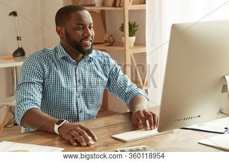 Successful Businessman Working Remotely. Cheerful Young Afro American Man In Shirt Working On The Co