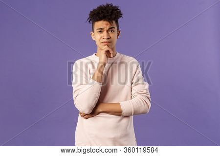 Thoughtful, Skeptical Young Man Look Judgemental And Hesitant At Camera While Pondering Between Choi